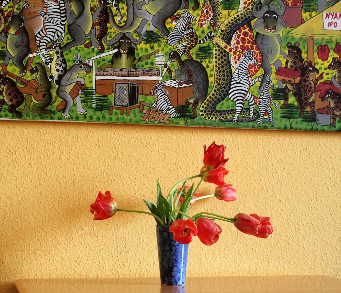 Blume auf Tisch vor gelber Wand